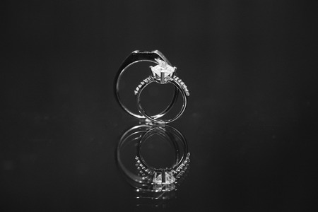 Close up shot of couple wedding diamond white gold ring for bride and groom, stand up on reflective surface. Black and white color with added noise grain. Standard-Bild