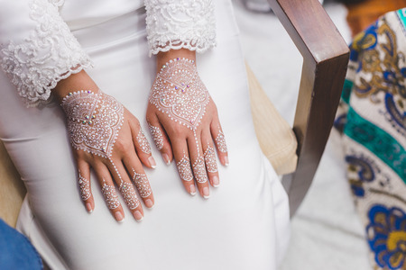 Beautiful and artistic henna decoration on bride hand. This is a traditional ceremony before bride getting married.