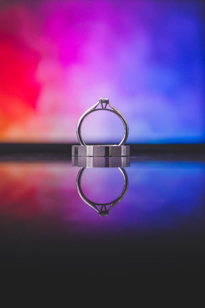 Close up of beautiful titanium ring given by groom to the bride on wedding day. Isolated on colorful background with reflection on glass surface.