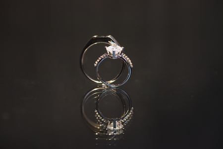 Close up shot of couple wedding diamond white gold ring for bride and groom, stand up on reflective surface.