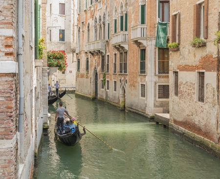 punting: Venetian gondolier punting gondola through green canal waters of Italy Editorial