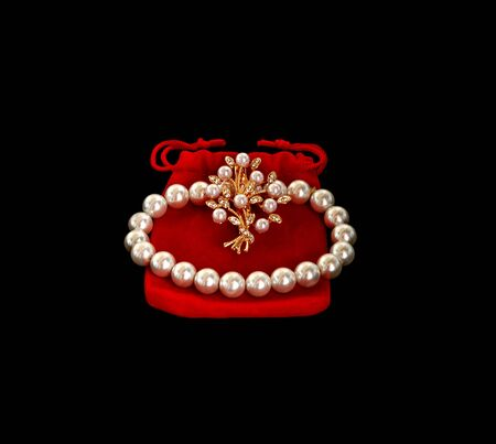 Bijouterie. White pearl bracelet and brooch on a red case. Banque d'images - 131978304