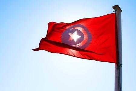 tunisian: Tunisian flag waving in the wind with sun behind
