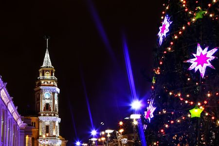 Illuminated and decorated tower and fir-tree in New Years Eve photo