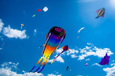 kite: Various kites flying on the blue sky in the kite festival Stock Photo