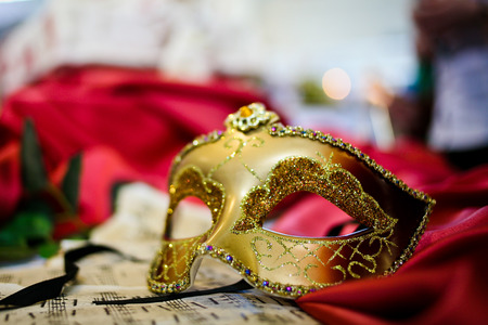 CARNAVAL: Femme masque de carnaval pose sur la feuille de musique close-up Banque d'images