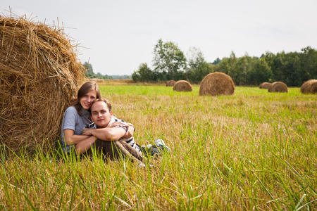 midst: Young loving couple on the haystack in the midst of rural meadow