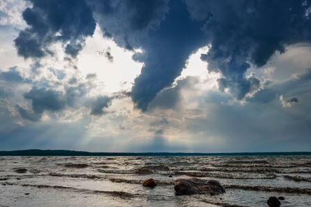 Storm clouds and sunbeams under lake before rain Stock Photo