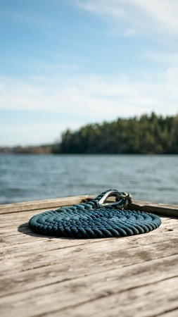 Coastal dock on a rocky area with blue nautical sailing rope for boats and yachts.