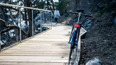 Hybrid sport street city bike on wooden pathway near water and rocky shore with blurred girl in background