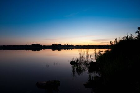 Summer evening during sunset. Calm lake and blue sky make pefect finnish summer. photo