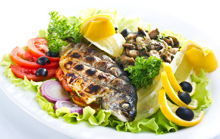 Grilled trout with lime and salad isolated on white photo
