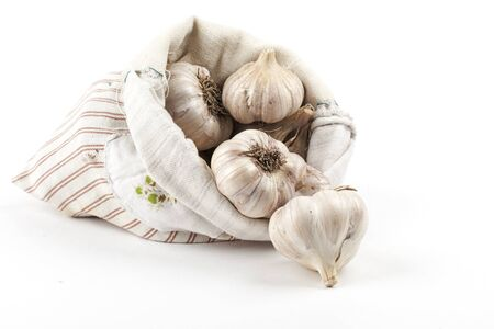 Striped cloth bag with garlic on a white background