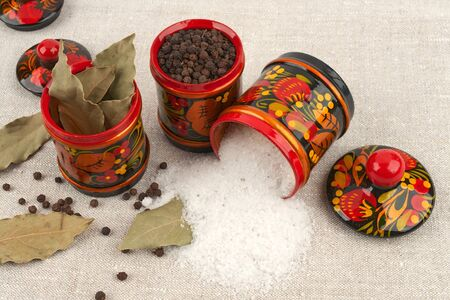 Khokhloma painted jars with salt, black pepper and bay leaf on a rough table cloth Stock Photo - 17251789