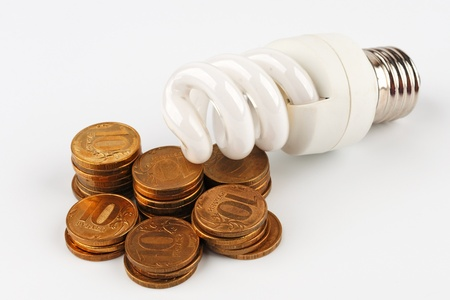 energy efficient: Energy saving light bulb lying on a pile of coins  On a white background  On a white background  Stock Photo