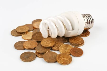 Energy saving light bulb lying on coins. On a white background.