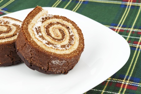 Swiss Roll With Cream on White Plate