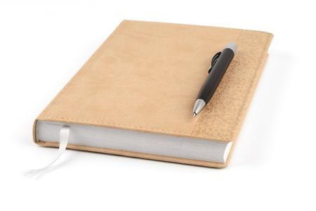 Black ballpoint pen on a beige diary on a white background Stock Photo