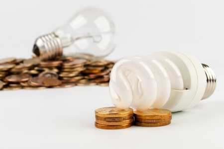 Energy saving lamp on the background of incandescent lamp with stacks of coins Archivio Fotografico