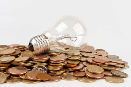 Incandescent lamp on the hill of coins Stock Photo