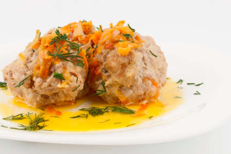 Meatballs on a white plate with a sprig of dill. Closeup