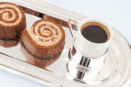 Several Swiss roll on the shiny metal tray with a cup of coffee Stock Photo - 17631589