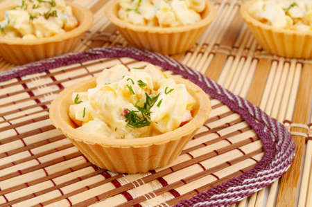 Tartlets with salad on a bamboo napkin