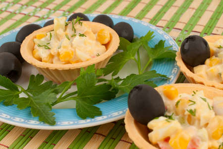 Tartlets with salad and olives on a blue plate