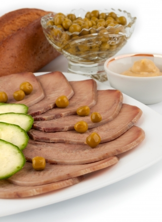 Slices of boiled beef tongue with green peas on white background photo
