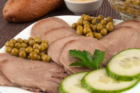 Slices of boiled beef tongue with green peas photo