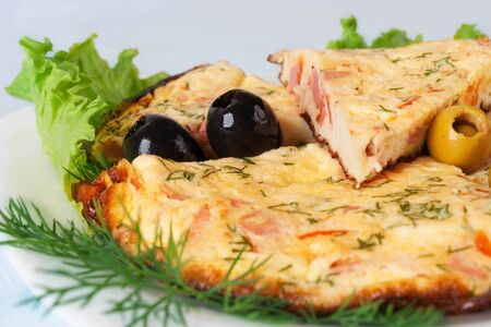 Slices of omelette with colorful olives