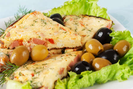 Slices of omelette with olives on lettuce leaf Stock Photo