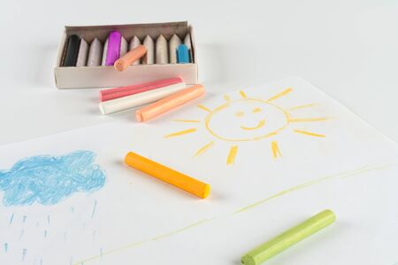 Children drawing pastel crayons  Sun and cloud  photo