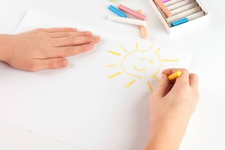 Child s hand drawing a pastel crayon smiling sun photo