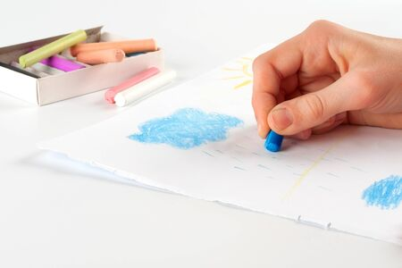 Child s hand, drawing a cloud of pastel crayon on white paper  Stock Photo