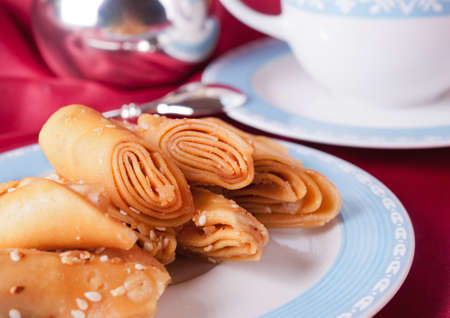 Puff pastry on a plate in front of a blue tea cup  photo