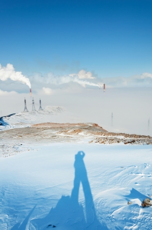 The shadow of a man standing on a mountain and looking at the smokestack smokestacks photo