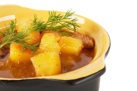 Stewed potatoes with meat, garnished with a sprig of dill photo