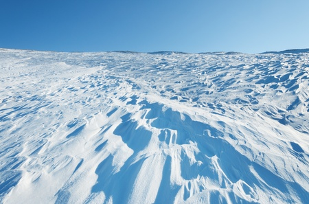 Snow waves on the hillside, on the background of blue sky