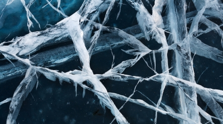 Network of cracks in thick solid layer of ice of a frozen river Stock Photo - 19110494