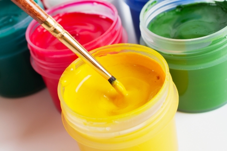 Colorful paint containers and a brush photo