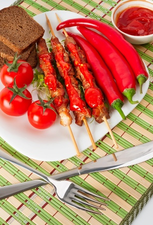 Shashlik on a plate with cherry tomatoes and chili  On a bamboo napkin