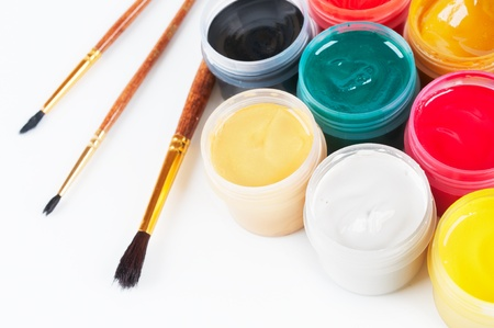 Jars with colored gouache and paint brushes  On a white background photo