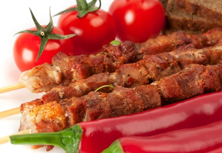 Shish kebab on bamboo sticks with cherry tomatoes and red pepper Stock Photo