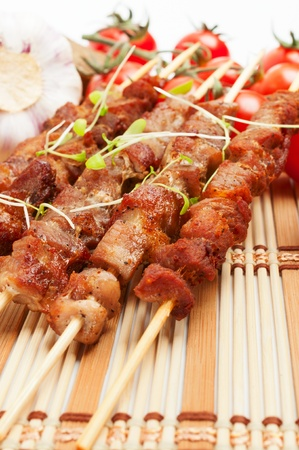 Pork skewers with cherry tomatoes, garlic and herbs  On a bamboo mat