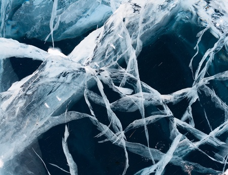 Network of cracks in thick solid layer of ice of a frozen river photo