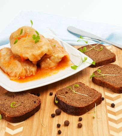 Cabbage rolls on a white plate with slices of rye bread