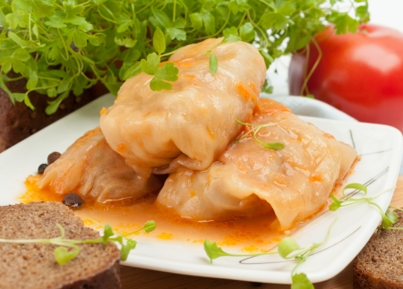 Cabbage rolls on a white plate with greens