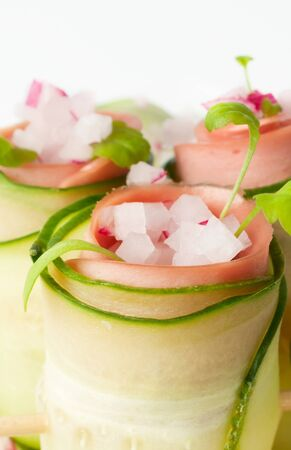 Cucumber rolls with cooked sausage, radishes and greens Stock Photo