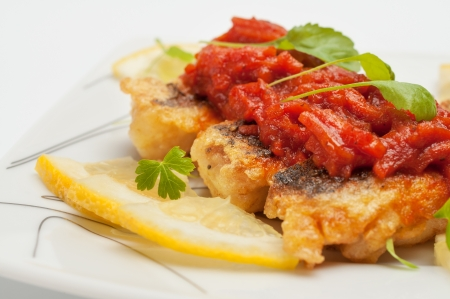 Pieces of fried fish with vegetable marinade  Closeup photo